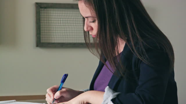 Close Up of Young Woman Writing on Documents