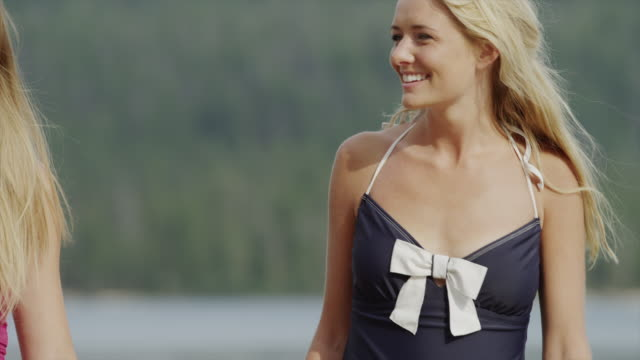 Close up of young women smiling and walking / Redfish Lake, Idaho, United States