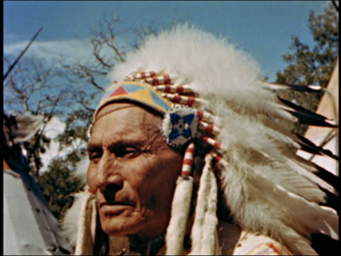 Close up older Native American man wearing headdress w/feathers / turning to look at CAM / AUDIO