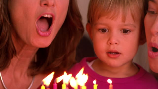 close up older woman, girl toddler + younger woman blowing out candles on birthday cake
