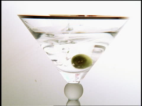 close up olive dropping in martini glass / white background - martini glass stock videos and b-roll footage