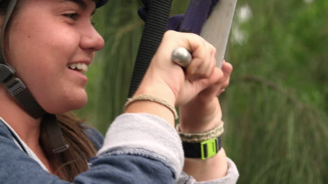 Close up on a girl's face as she prepares to launch off a zipline platform