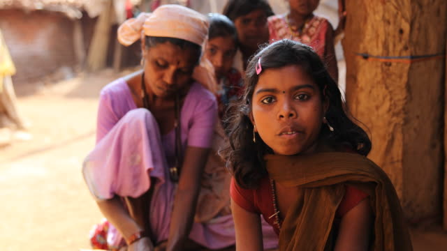 a close up on a little girl an older woman and other girls in the background sitting on the ground in a rural village in nashik a region located in... - maharashtra stock-videos und b-roll-filmmaterial