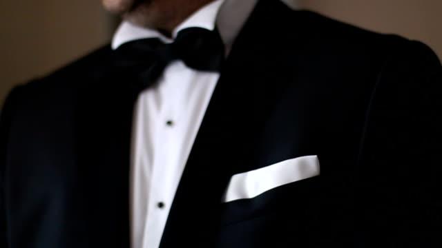 ein mann im schwarzen anzug und fliege hautnah - schleife stock-videos und b-roll-filmmaterial