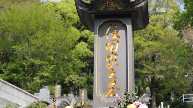 a close up on a memorial headstones with golden inscriptions in japanese - massenvernichtungswaffe stock-videos und b-roll-filmmaterial