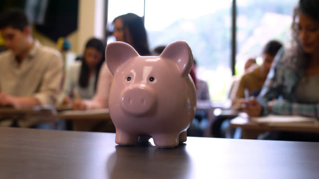 close up on a pink piggy bank and students at the background studying - post secondary education stock videos & royalty-free footage
