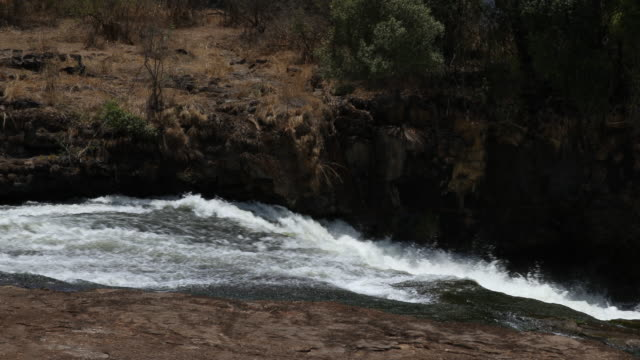 a close up on a strong water stream running downhill at victoria falls natural park - 景勝地点の映像素材/bロール
