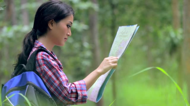 Close up on a young asian woman explorer looking at map, slow motion