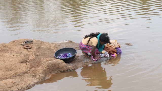 a close up on a young girl washing clothes at a water source within rural landscape in nashik a region located in the northwestern part of the... - hausarbeit stock-videos und b-roll-filmmaterial