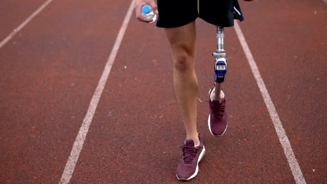 vídeos de stock e filmes b-roll de close up on amputee male walking on sports track and getting ready to workout - disability