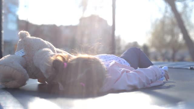 närbild på baby liggande i mini studsmatta - flickbaby bildbanksvideor och videomaterial från bakom kulisserna