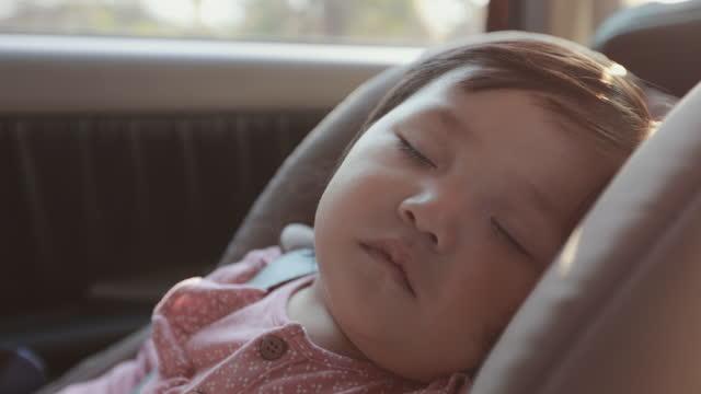 vidéos et rushes de fermez-vous vers le haut sur la fille asiatique mignonne d'enfant en bas âge se reposant sur le siège d'auto et dormant tout en voyageant avec la famille dans le projectile de ralenti. - sûreté