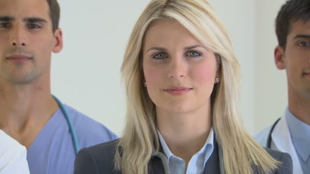 Close up on face of female doctor, camera pulls back to reveal five healthcare professionals