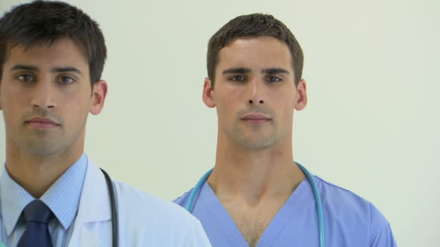 close up on face of surgeon, camera pulls back to reveal five healthcare professionals - zoom out stock videos & royalty-free footage