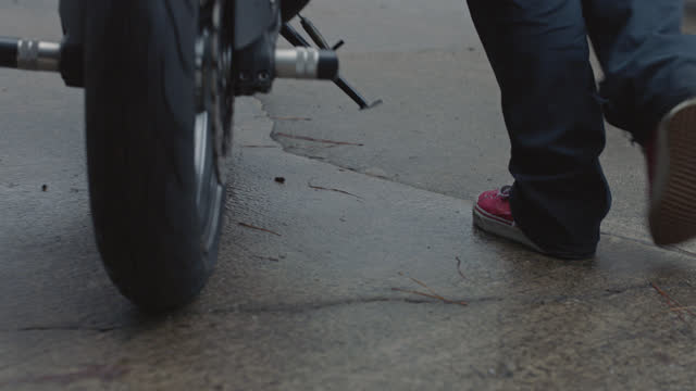 close up on feet and wheels as man rolls motorcycle out of garage and into driveway. - garage stock-videos und b-roll-filmmaterial