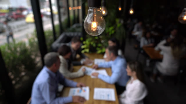 close up on foreground of a lightbulb while business people are in a meeting - cafe stock videos & royalty-free footage