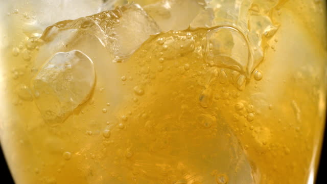 Close up on glass full of yellow carbonated drink
