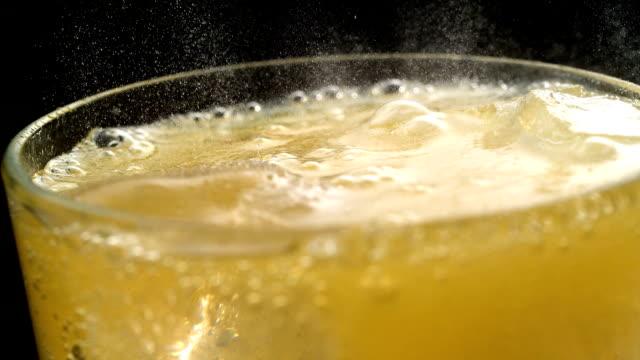 vidéos et rushes de gros plan sur le verre plein de boissons gazéifiées jaune - orange