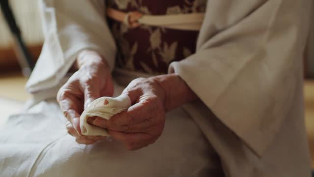 vídeos de stock, filmes e b-roll de feche acima nas mãos do anfitrião japonês da cerimónia do chá - washitsu