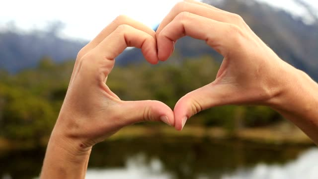 close up on human hands making a heart shape finger frame on mountain lake landscape - human finger stock videos and b-roll footage