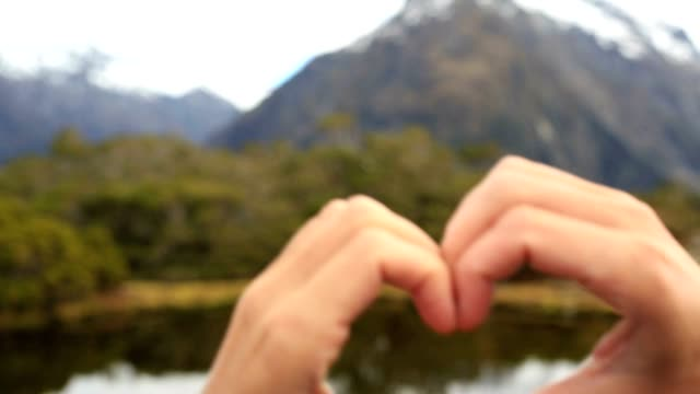 close up on human hands making a heart shape finger frame on mountain lake landscape - human finger stock videos & royalty-free footage