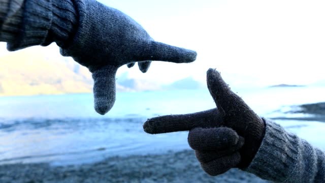 Close up on human's hands framing mountain lake landscape