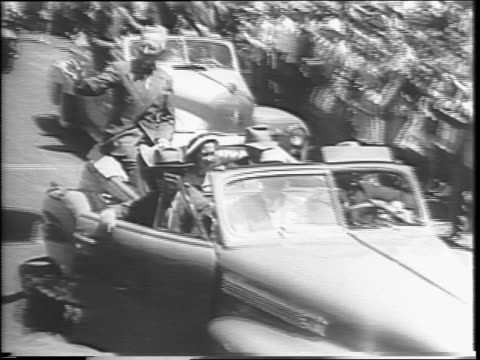 stockvideo's en b-roll-footage met close up on older man's face / street view with crowds at the side of the street ready for a parade / montage of president harry s truman in a car... - margaret truman