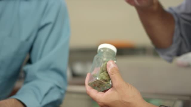 Close-up op de handen van een medewerker in een marihuana winkel met een product