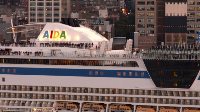 close up on tourists aboard aida cruise ship leaving port in new york city - kreuzfahrt stock-videos und b-roll-filmmaterial