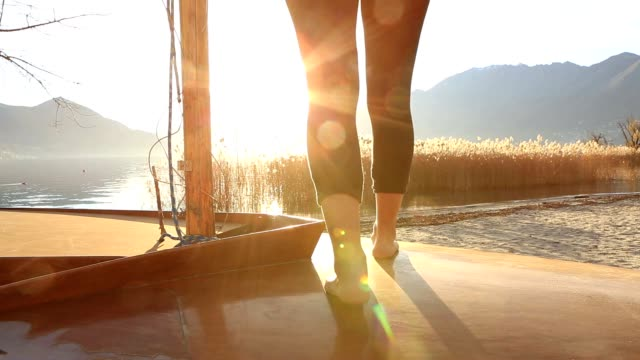 Close up on woman's feet standing on boat above lake