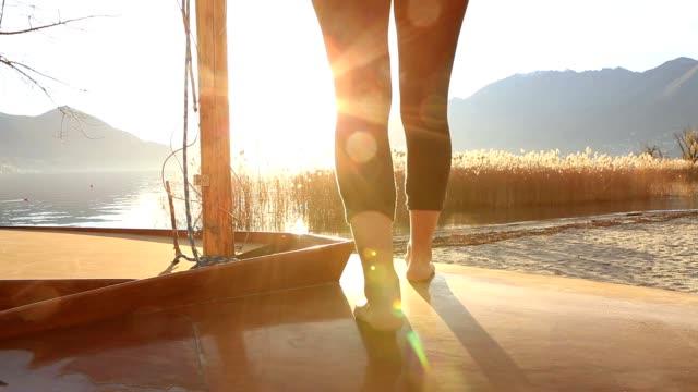 ボートは湖の上に立っている女性の足のクローズ アップ