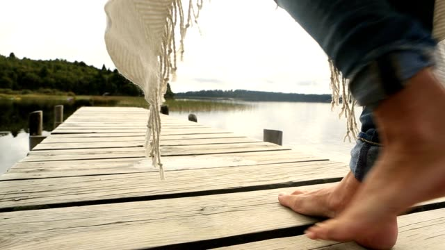 close up on woman's feet standing on jetty above lake - barefoot stock videos & royalty-free footage