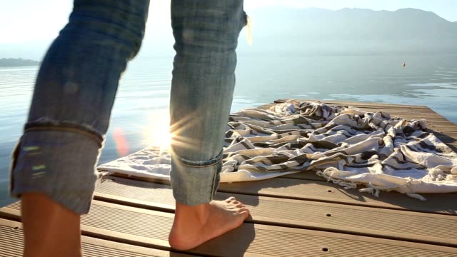 Close up on woman's feet walking on jetty above lake