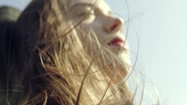 close up on woman's hair blowing in wind while riding in convertible car. close up - red lipstick stock videos & royalty-free footage