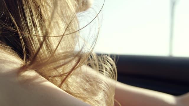 stockvideo's en b-roll-footage met close-up op vrouw haar waait in de wind tijdens het rijden in cabriolet auto. close-up - chauffeur beroep
