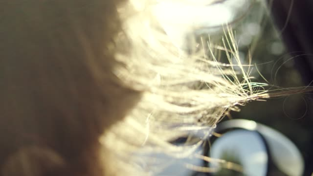 close up on woman's hair blowing in wind while riding in convertible car. close up - convertible stock videos & royalty-free footage
