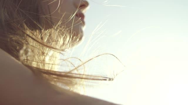 コンバーチブルカーに乗りながら風に吹かれる女性の髪をクローズアップ。クローズアップ - 人間の唇点の映像素材/bロール