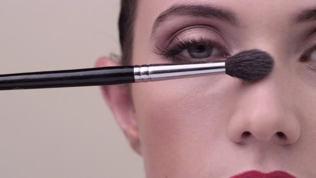 vídeos y material grabado en eventos de stock de ecu close up on young woman face as shes being made up - sombreador de ojos