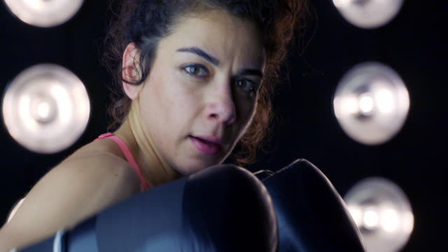 close up on young woman in boxing gloves punching at camera 4k - vesper stock stock videos & royalty-free footage
