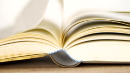close up opened book on the table , wind turning the book page ,reading textbook or  learning education concept