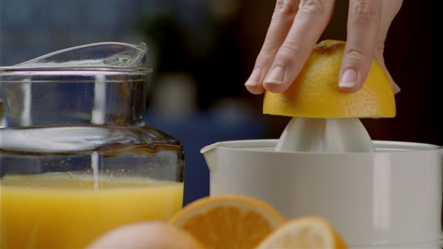 close up orange half being juiced with mechanical juicer - bricco video stock e b–roll