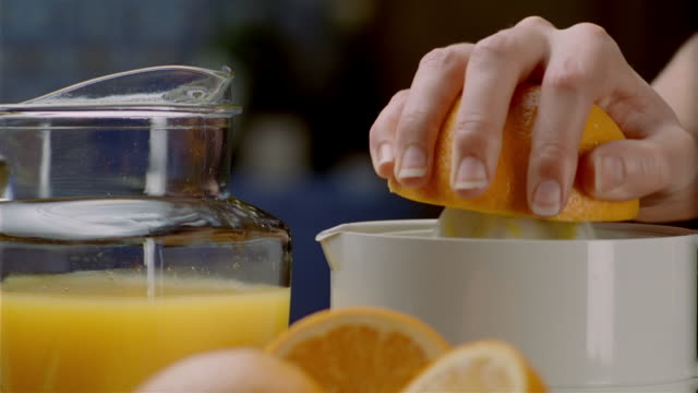 close up orange half being juiced with mechanical juicer - pour spout stock videos & royalty-free footage
