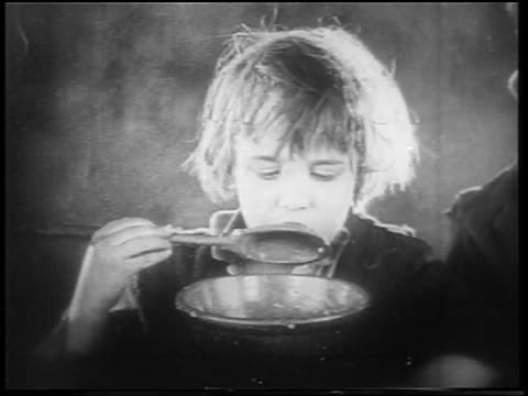vidéos et rushes de b/w 1922 close up orphan boy (jackie coogan) eating gruel with large spoon + looking sad / feature - orphelin