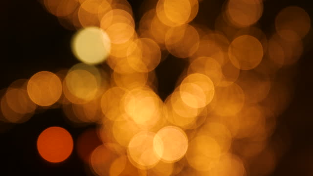 close up out of focus shot of gold lights at night - defocussed stock videos & royalty-free footage