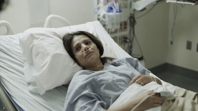 close up over the shoulder view of nurse talking to patient in hospital bed / salt lake city, utah, united states - incidental people stock videos & royalty-free footage