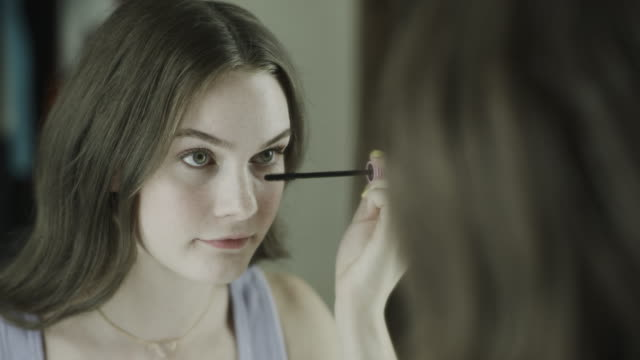 vidéos et rushes de close up over the shoulder view of reflection of woman applying mascara / cedar hills, utah, united states - mascara