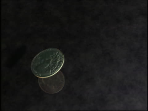 cgi close up overhead american quarter flipping + bouncing on grey background - quarter stock-videos und b-roll-filmmaterial