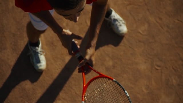 close up overhead slow motion of man twirling tennis racket - tennis stock videos & royalty-free footage