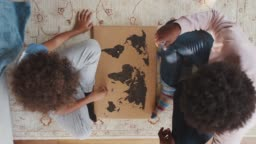 Close up overhead view of a mixed race pre teen boy and his father sitting cross legged on the floor opposite each other playing an educational game with a world map and map pins