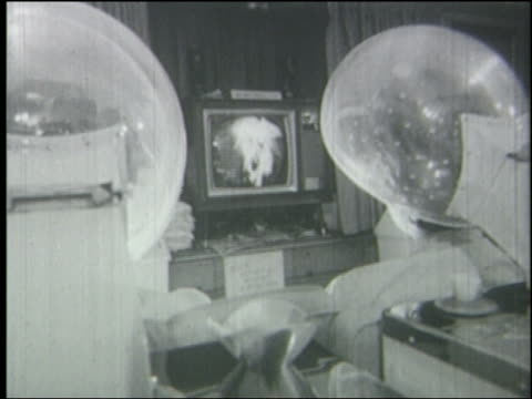 B/W 1965 REAR VIEW close up over-the-shoulder 2 women sitting under hair dryers watching television